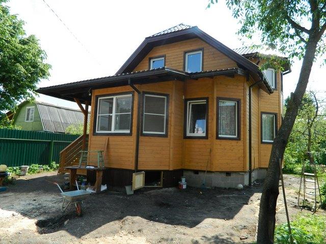 Обычный загородный дом, с отделкой сайдинга под дерево. Также в доме установленные коричневые пластиковые окна